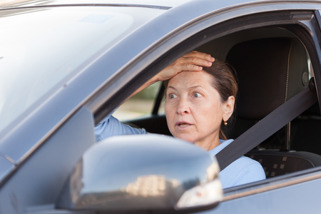 Portrait of frightened senior woman in  black car.