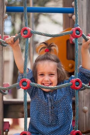 deftness: little girl climbing the ropes of challenge net at playground Stock Photo