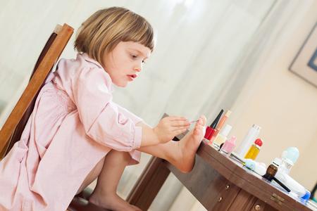three year old: Beautiful three year old girl making pedicure Stock Photo