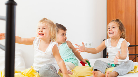 Three young children playing on  bed in  bedroom. photo