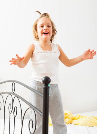 cheerful girl    playing on  big bed. photo