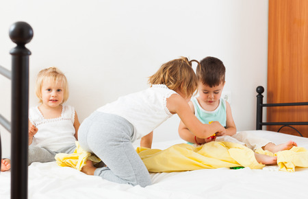 Two sisters and  brother having fun in white bed. photo