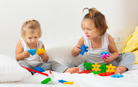 little kids playing on  white bed photo