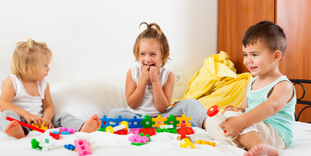 Three little children playing on  bed in  bedroom. photo