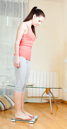 losing control: cheerful girl standing on bathroom scales at home interior