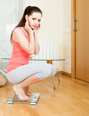 underweight: serious girl  on bathroom scales at home interior Stock Photo