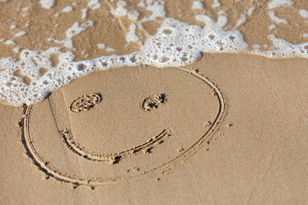 smily face: funny face  drawning  on  sand near  sea