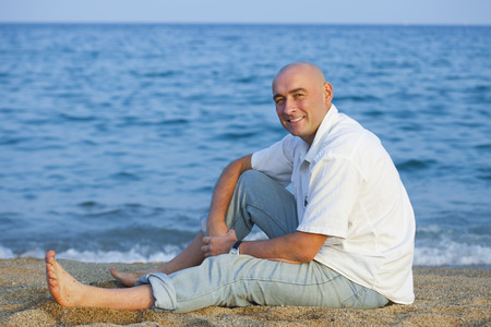 man sitting on  sandy beach near  sea.