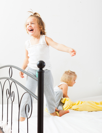 Two sisters  having fun in white bed. photo