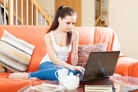 woman using laptop on sofa  in home photo