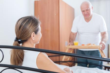 elderly husband brings his wife breakfast in bed. photo
