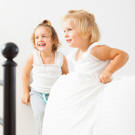 Little children playing on  bed in  bedroom. photo