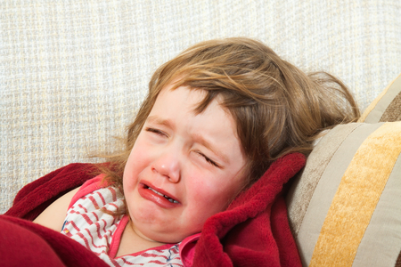 frustrated child lying on the couch under a blanket photo