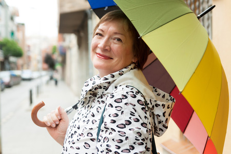 Happy mature woman in jacket outdoors in autumn Stock Photo
