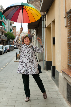 pensionary: Portrait of  funny mature woman with umbrella in autumn