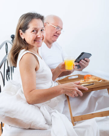 breakfast in bed: Woman and man sitting on  white bed near tray with breakfast .