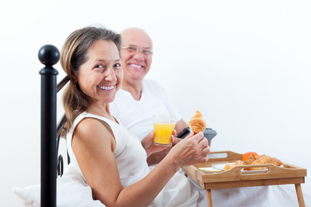 bed and breakfast: Smiling elderly husband brings his wife breakfast in bed. Stock Photo