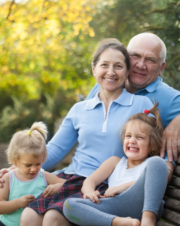 beautiful mature couple with children sitting on bench in autumn park. Stock Photo