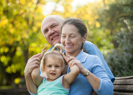 grandaughter: Portrait of grandma and  grandpa with little grandaughter  outdoor Stock Photo