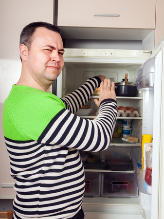 rancid: Handsome man looking for something in refrigerator  at kitchen
