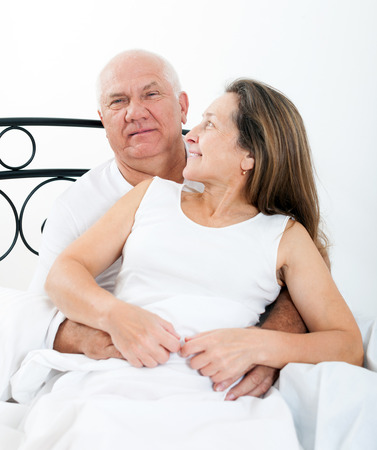 Beautiful elderly couple embracing in bed. photo