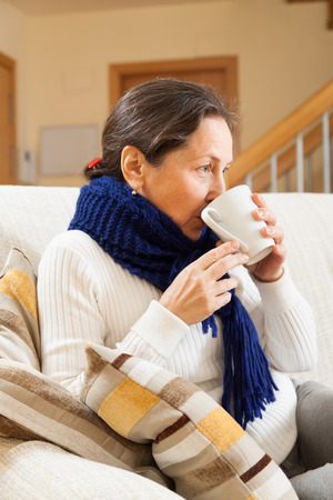 unwholesome: Mature illness woman drinking hot tea at home
