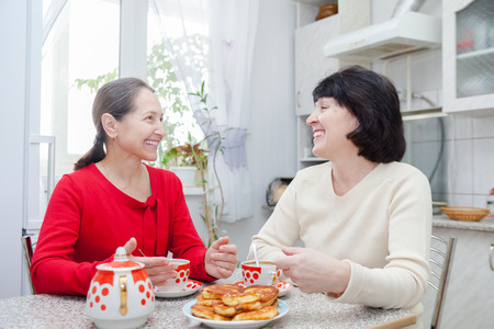 Happy mature women talking over coffee in   kitchen. Stock Photo