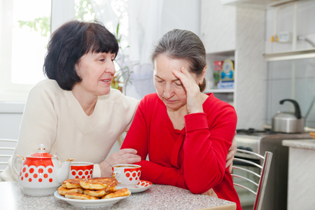 Two mature women talking at   kitchen table with   cup of tea. Stock Photo