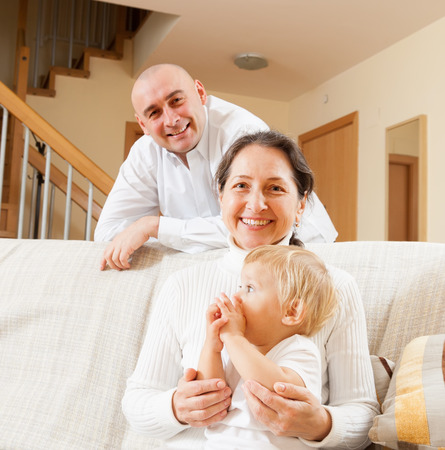 grandkid: Two adult people with little girl at home
