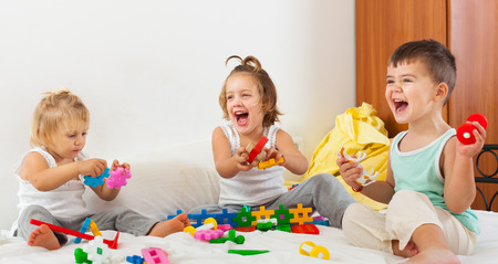 Two  girls and a boy playing on  big bed. photo