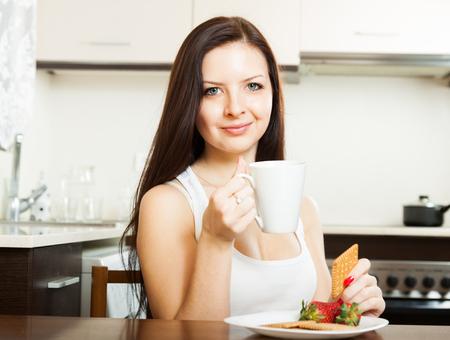 mujer tomando cafe: Mujer joven bebiendo té con galletas y fresas