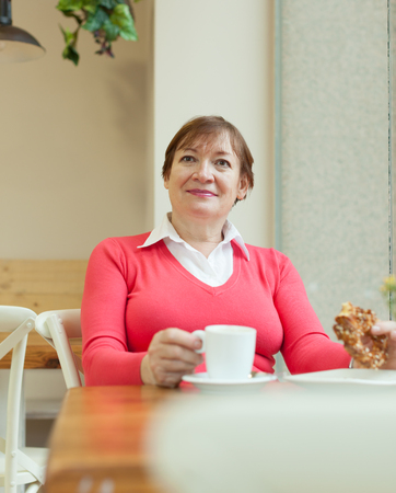 Elderly woman sitting in   cafe with   cup of coffee and   bun. photo