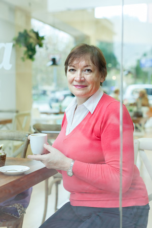 Elderly woman sitting in   cafe at   table. photo