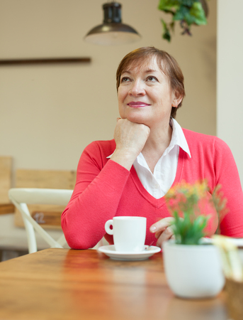 Portrait of senior  woman    sitting at   table in   cafe. photo