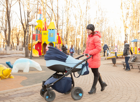 young mother with baby in stroller walking in   park. photo