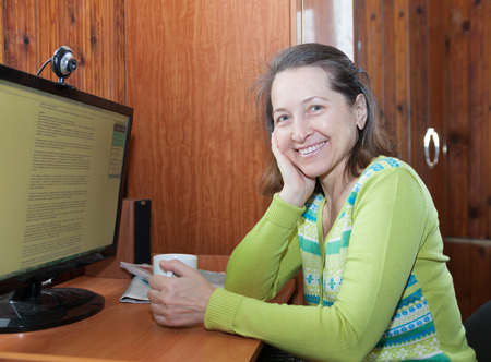 Portrait of  beautiful middle-aged woman near home computer photo
