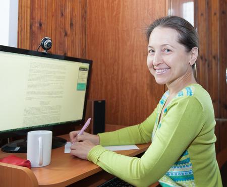beautiful elderly woman sitting at computer at home. photo