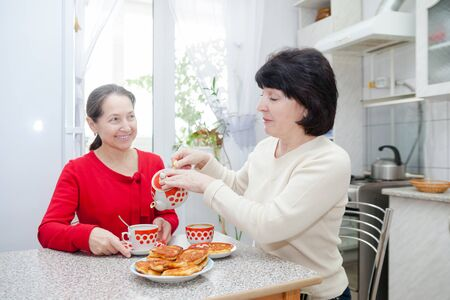 mature women: Two mature women talking over coffee in   kitchen.