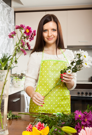 Beautiful girl with flowers on  kitchen table photo