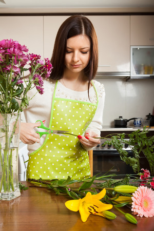 Beautiful girl with flowers on  kitchen table Stock Photo