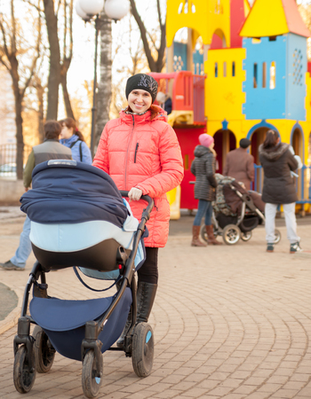 niño empujando: joven madre con el bebé en el cochecito que recorre en el parque.