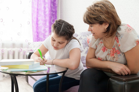 learning by doing: Mature mother helping her child with homework at home.