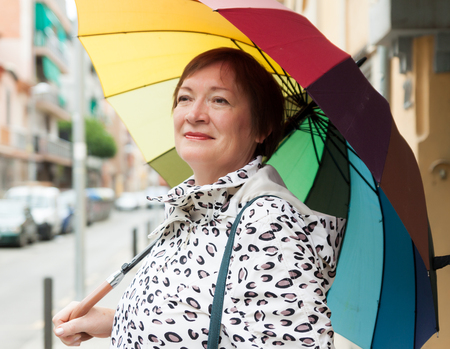 pensionary: portrait of mature woman with umbrella in autumn