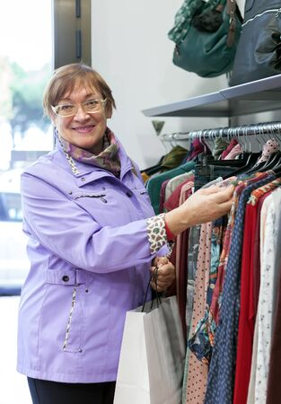 clothing store: Mature woman choosing   purchase in clothing store.