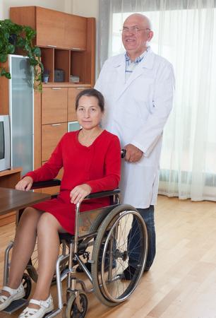silla de ruedas: mujer madura en silla de ruedas y adulta masculina médico cercano. Foto de archivo