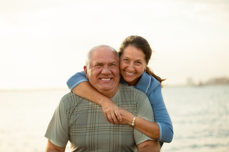 Senior couple on  beach in  sunset rays of  sun. Stock Photo