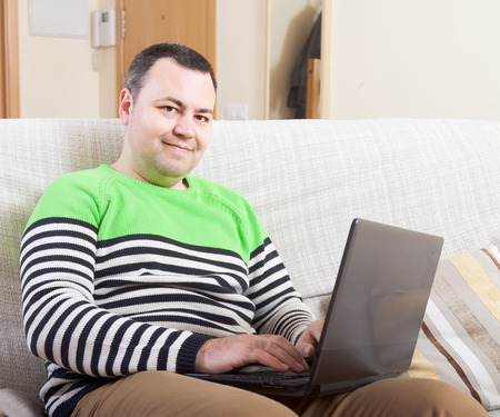 work from home: man  sitting at work on laptop at home. Stock Photo