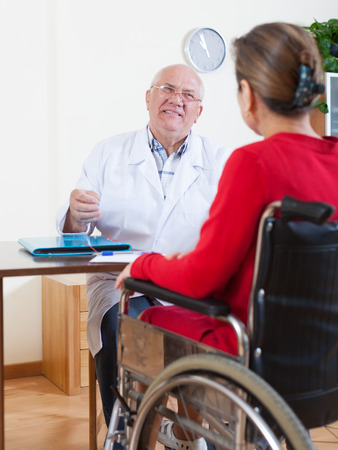 adult male: mature woman in   wheelchair and   adult male doctor nearby.
