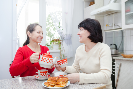 friends coffee: Two mature girlfriends talking over coffee in  kitchen.