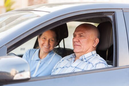 taking a wife: Elderly man taking his wife in  car. Stock Photo